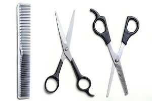 Two open scissors and comb barber