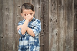 Frustrated Mixed Race Boy With Hand