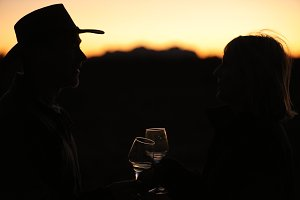 Couple making toast during sunset