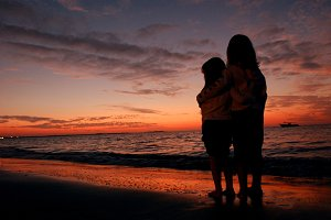 Young sisters on beach during sunset