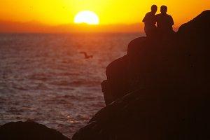 Couple on cliff watching sunrise