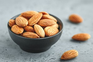 Fresh almond nuts in a back bowl