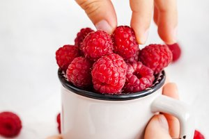 Fresh ripe raspberries in a mug in c