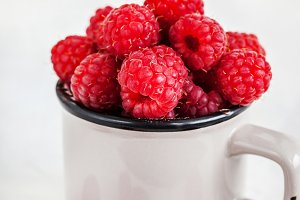 Fresh ripe raspberries in a mug on w