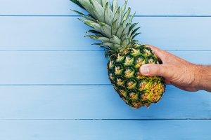 Pineapple fruit held in hand