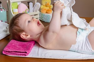 Baby lying playing with small towel
