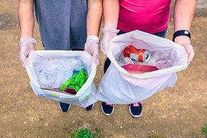 Plogging. Girls showing garbage
