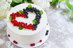 Round white cake with berries in the