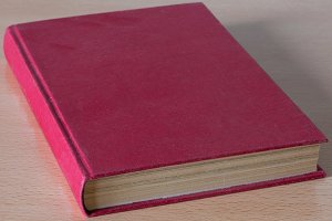A red book on a wooden table