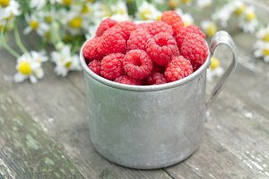Vintage mug full of raspberriies