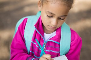 Close-up of girl writing in book