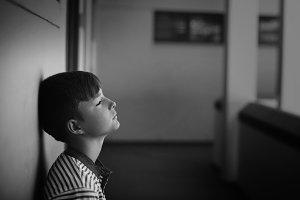 Sad schoolboy leaning head