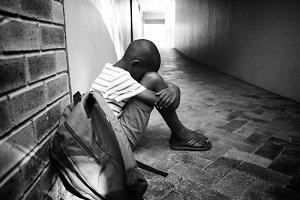 Boy sitting alone on school corridor