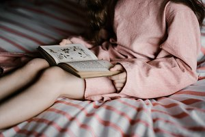 Child sat on bed, reading