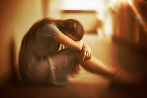 Sad schoolgirl sitting in corridor
