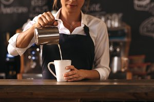 Female barista making a cup