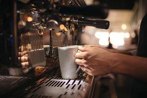 Female cafe worker preparing coffee