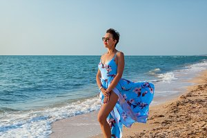 girl on the beach in a dress near th
