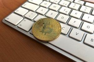 bitcoin over a white computer keyboa