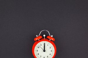 Red vintage alarm clock on dark back
