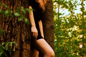 girl in a deciduous forest sits on a