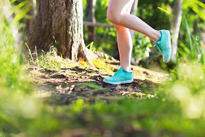 Young woman run in summer forest in