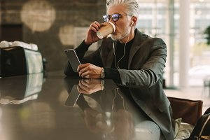Businessman with phone drinking