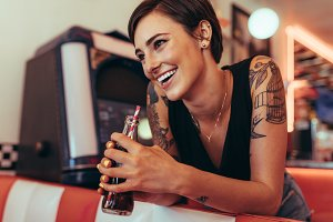 Smiling woman holding a soft drink