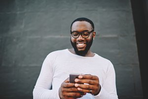 Smiling hipster guy hold smartphone