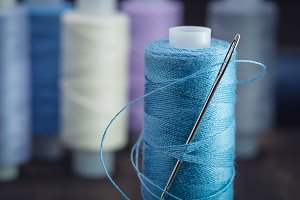 Reel of blue threads with  needle.