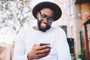 Happy hipster guy using mobile phone