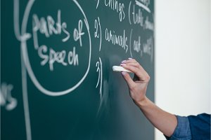 The teacher writes English rules on