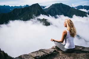 Female meditating yoga in mountains