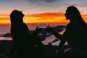 women drink wine together at sunset