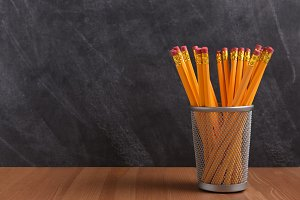 A pencil cup in front of a blackboar