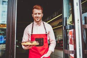 Man barista or bakery owner at door