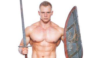 Bodybuilder man posing with a sword