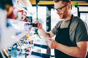 Male barista make coffee on machine