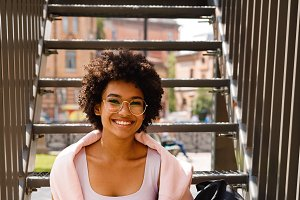 Happy student sitting on staircase