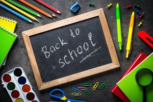 School and office supplies on black