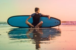 Silhouette of surf man sitting with
