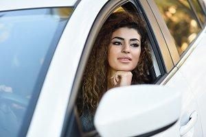 Young Arab woman inside a car
