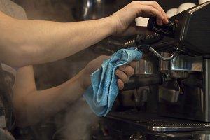 waiter cleaning coffee machine