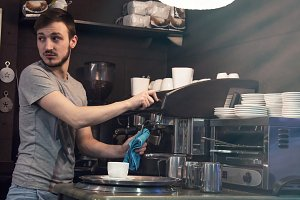 waiter cleaning coffee machine