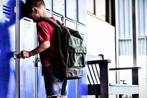 Full length of boy leaning on locker