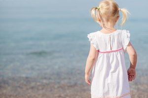 Small girl standing at the shore of