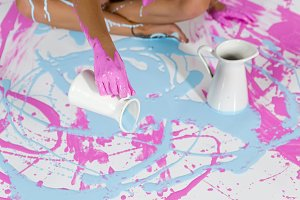 girl pours blue paint from a jug