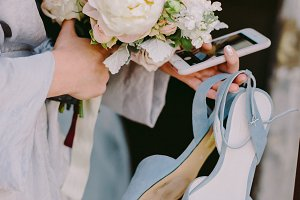 bride holding bouquet smartphone and