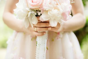 bride holding wedding bouquet of flo