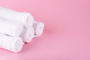 White spa towels pile on pink backgr